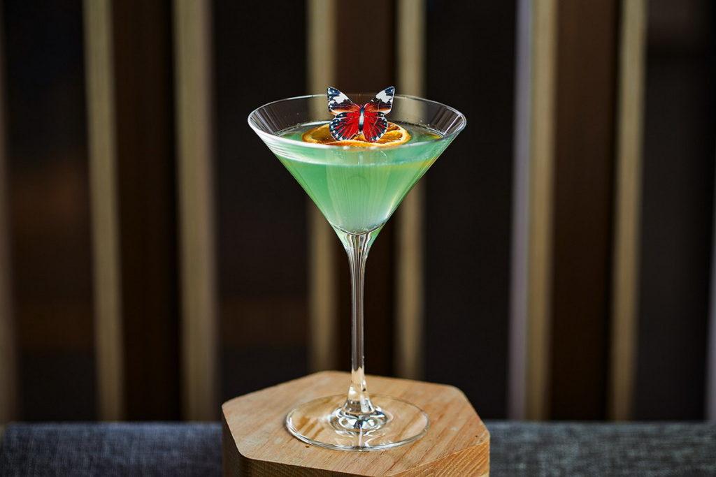 「花園撲蝴蝶」以琴酒為基底,搭配自製蜜瓜及接骨木糖漿,整體意象宛如小時候到戶外踏青,春意盎然蝴蝶滿天飛舞的景象。(圖/台北新板希爾頓提供)